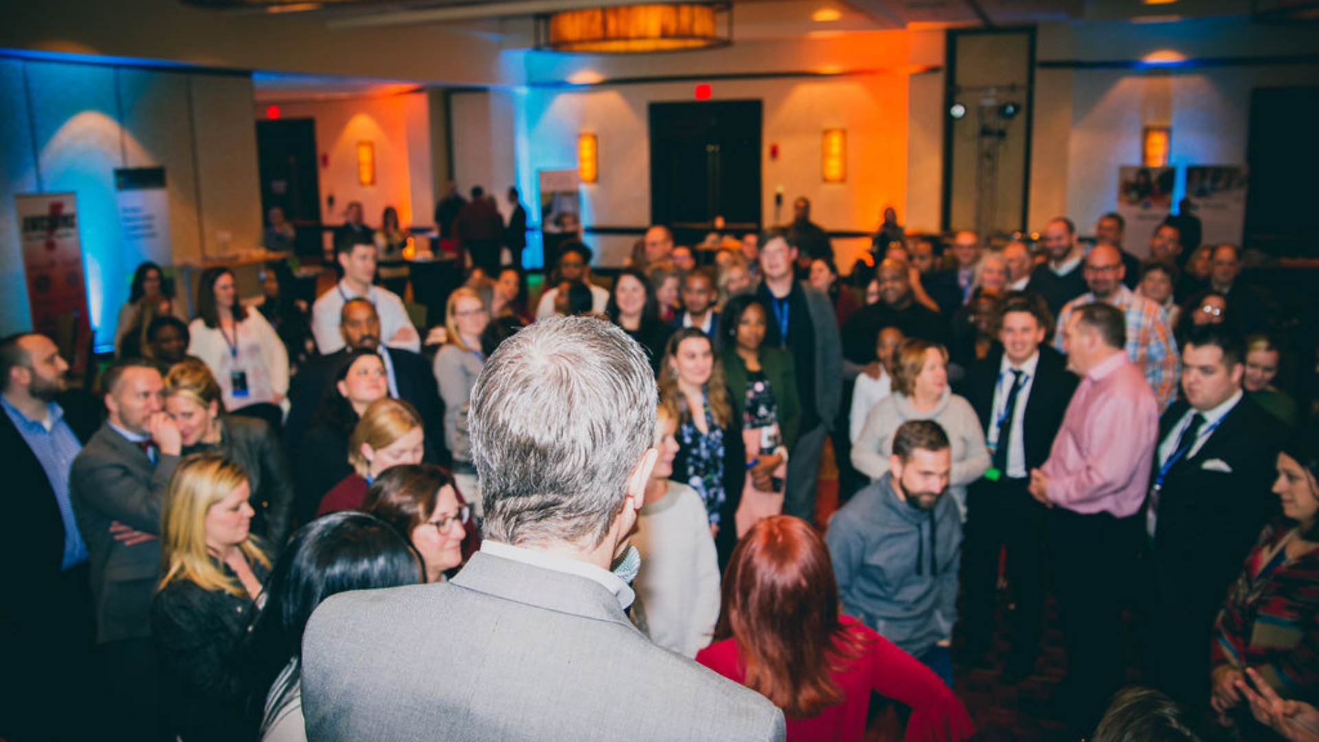 A photo of MAPSA President, Dan Quisenberry, facing away from the camera and towards a small crowd of charter school stakeholders who are attending the 2019 MAPSA Social.