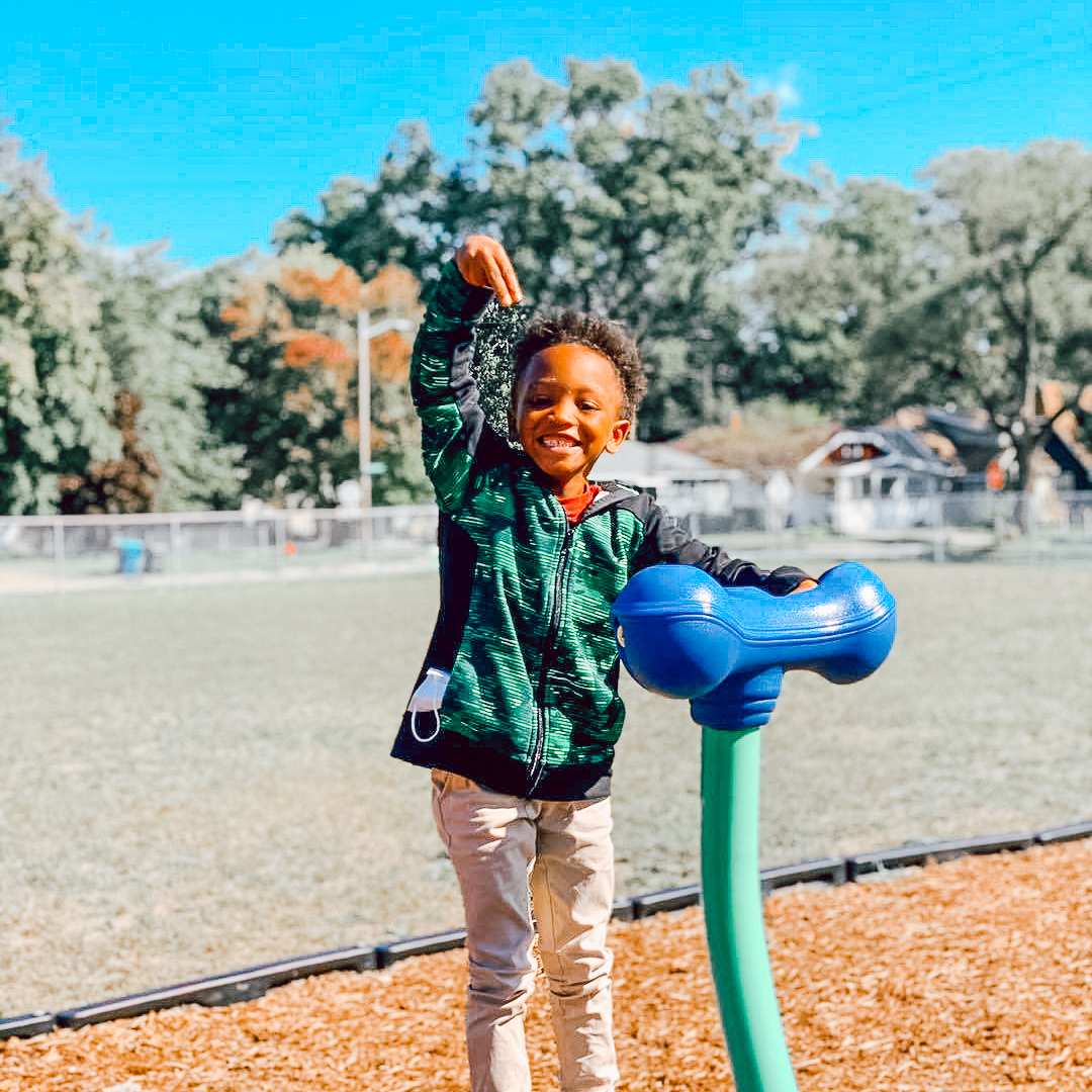 An African American student plays with wood chips on a playground