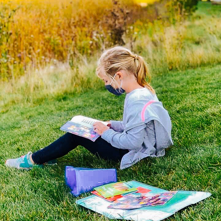 A photo of a MI charter school elementary student, reading in the grass, masked.