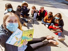 A teacher takes a selfie style photo holding two books sitting on the sidewalk with a half circle of students .