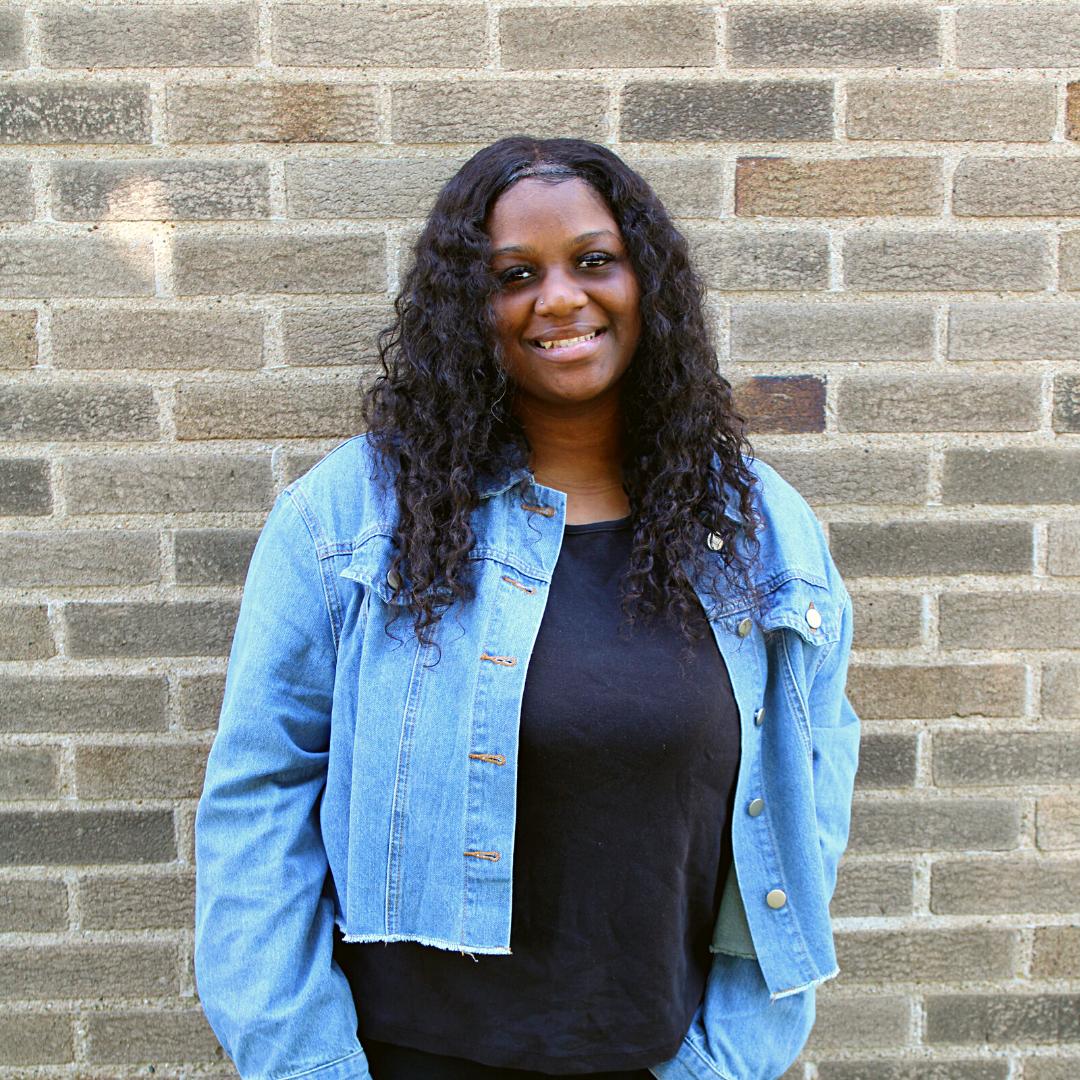 A photo of a high school Michigan charter school graduate, smiling.
