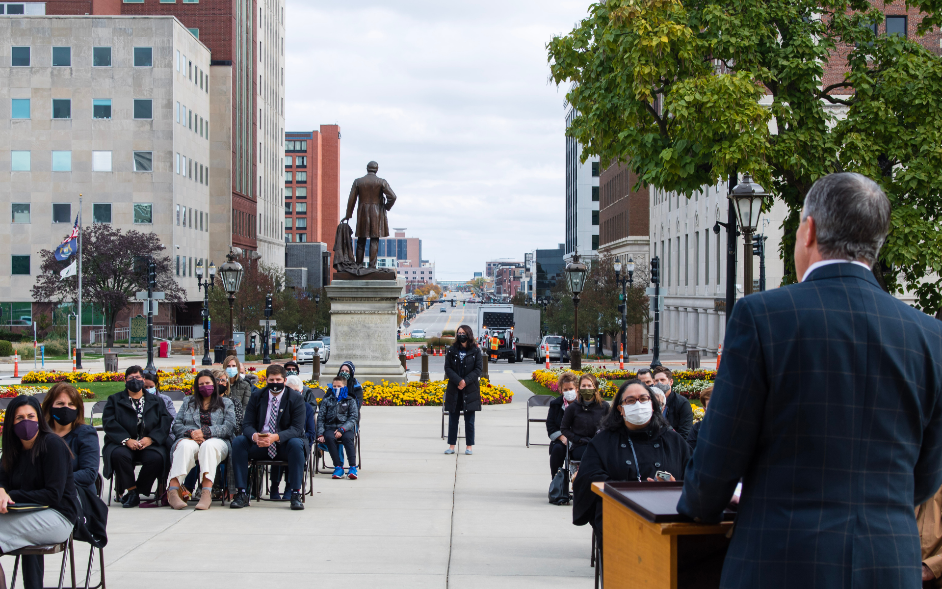 A photo of several small groups of people, seated and masked on the Michigan Captiol lawn, with MAPSA President, Dan Quisenberry facing away from the camera, delivering remarks to the group.