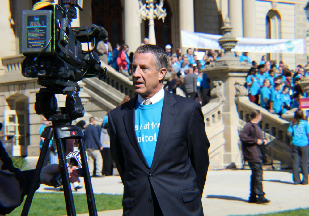 A photo of MAPSA President Dan Quisenberry being interviewed by media during the 2017 Charter Day at the Capitol celebration.