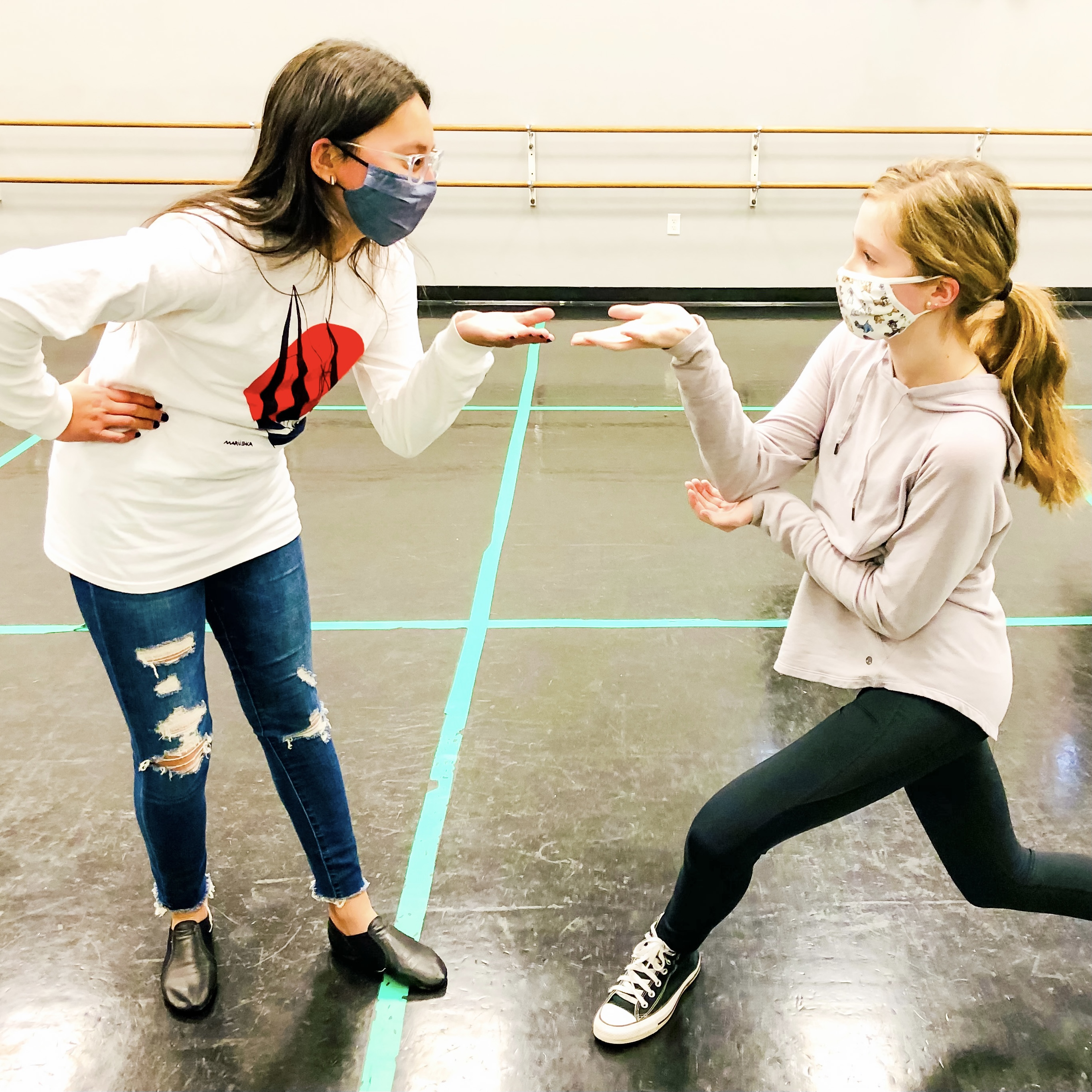 Two students stand facing each other in the middle of musical theatre practice