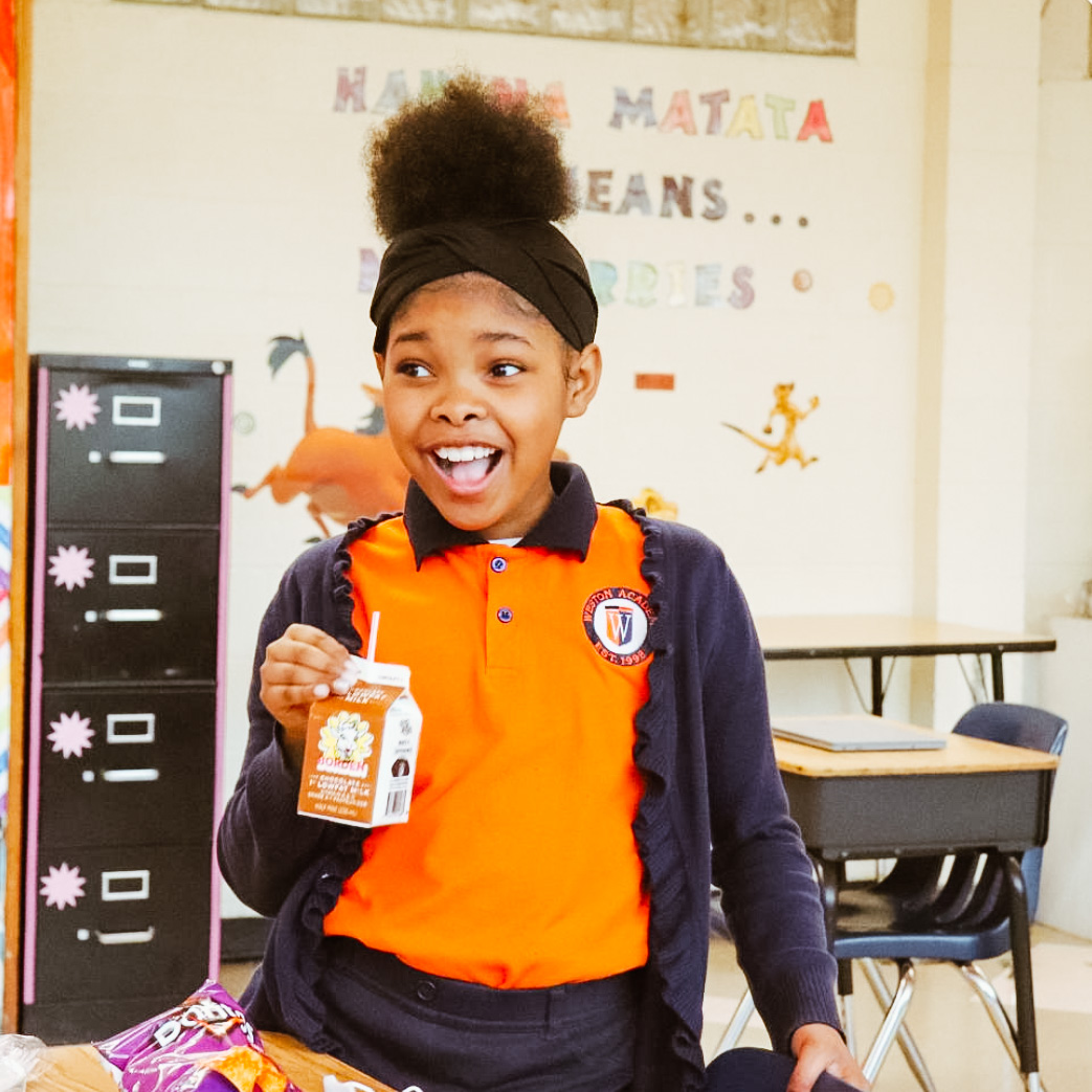 A photo of a female African American student stands with her mouth open with joy.