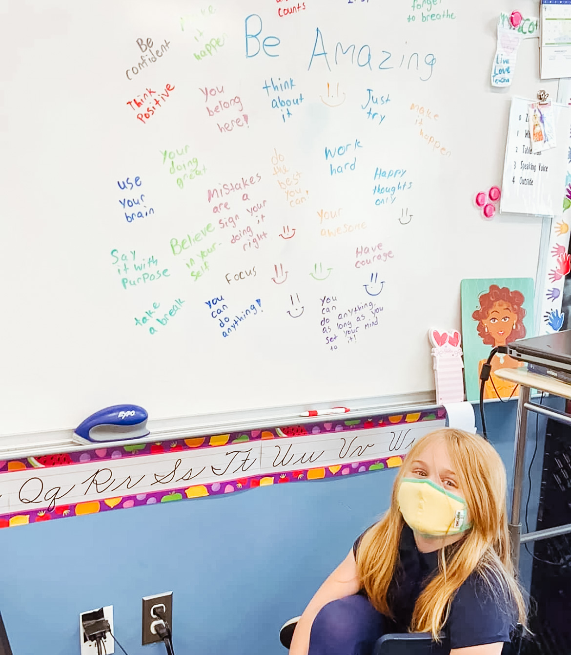 A female student sits in front of the white board where she wrote encouraging words for her classmates.