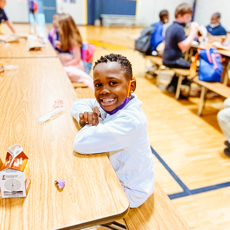 A photo of an elementary-aged, Black male student smiling with elbows resting on a cafeteria table.