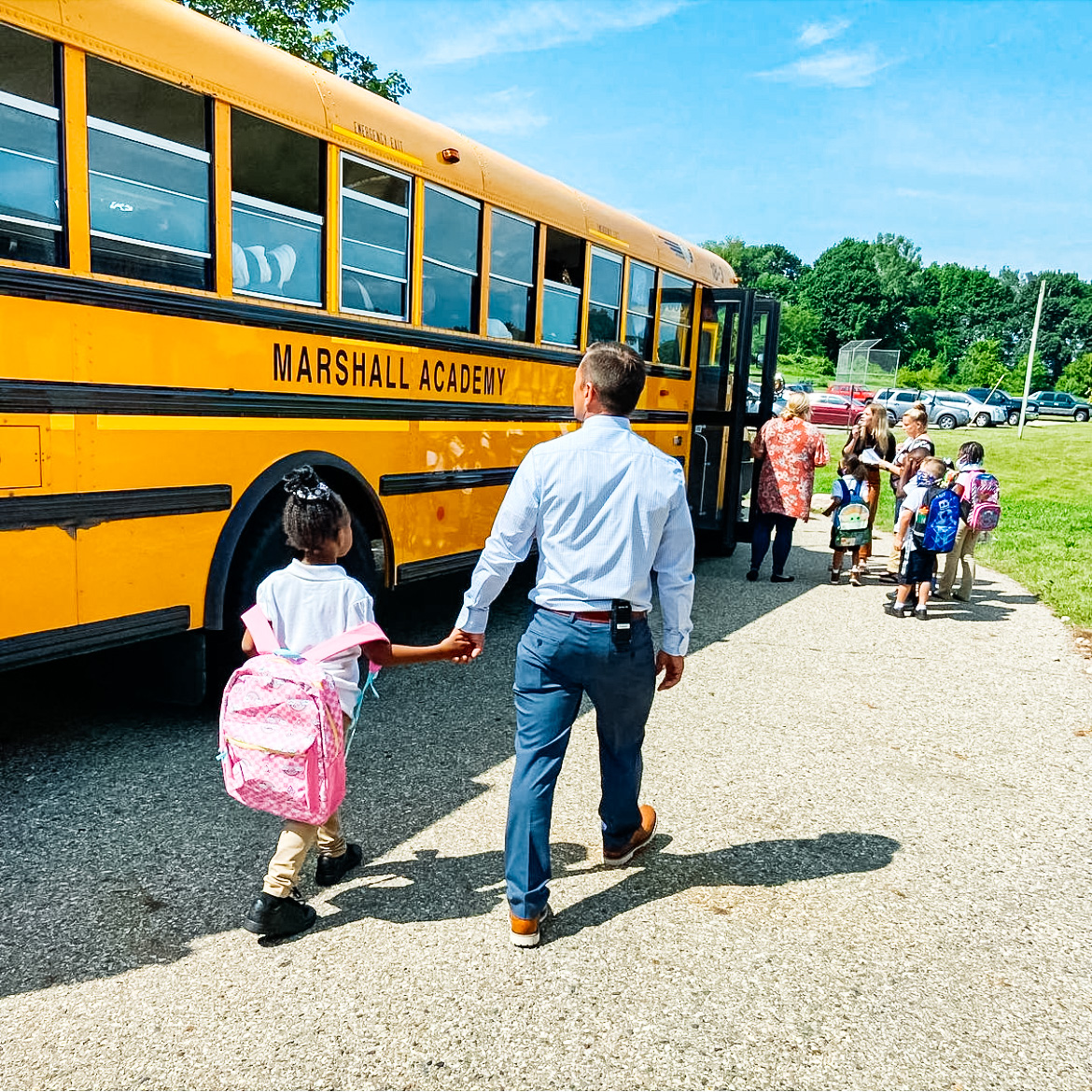 The principal from Marshall Academy walks a student to the bus