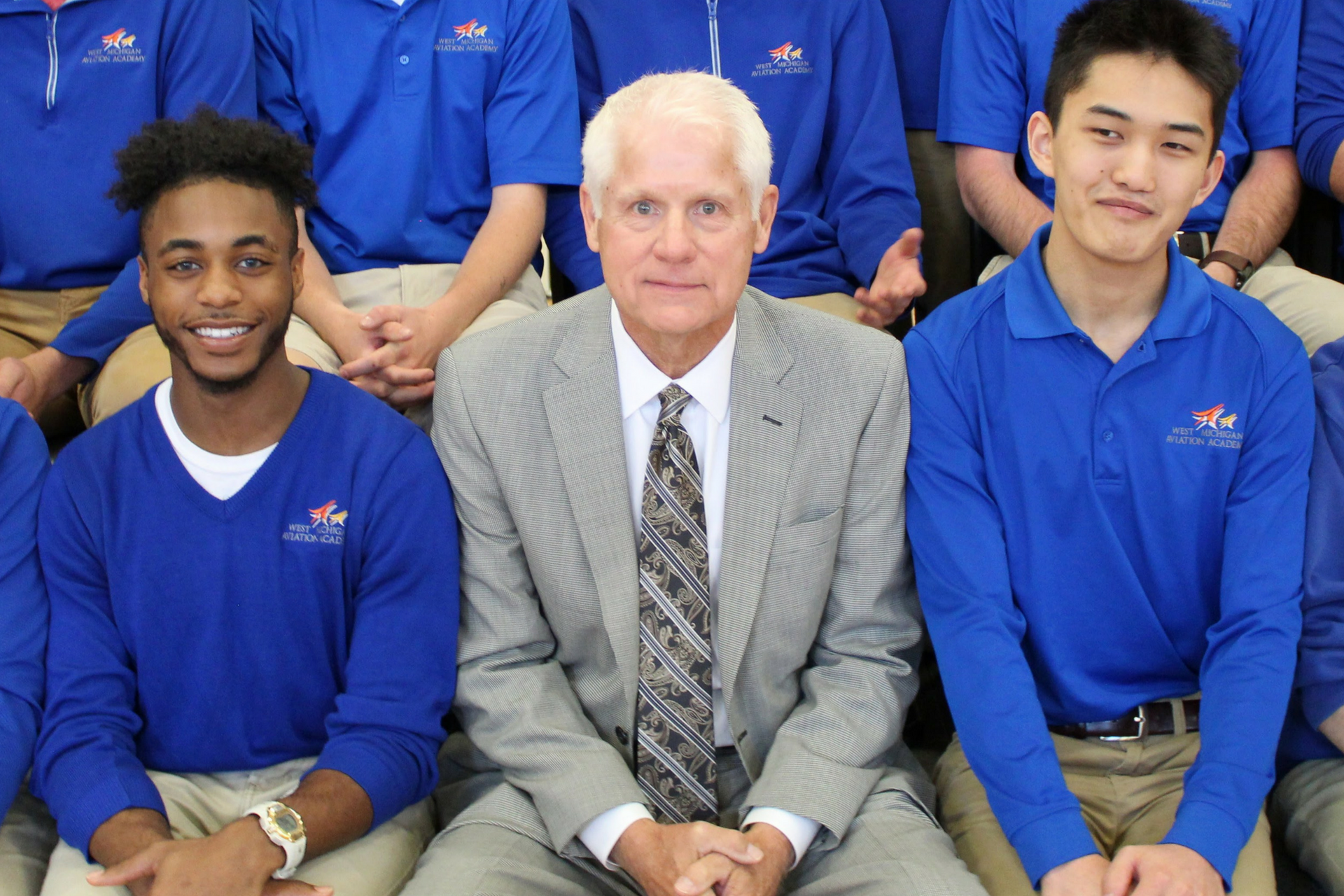 A photo of West Michigan Aviation Academy school leader, and 2018 Charter School Administrator of the Year recipient, Pat Cwayna, surrounded by students at a pep rally.