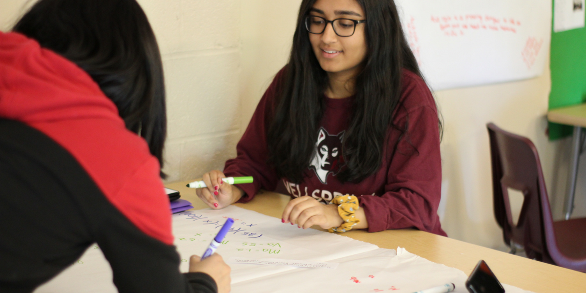 A photo of two female students practicing math equations at their desks using white paper and markers.