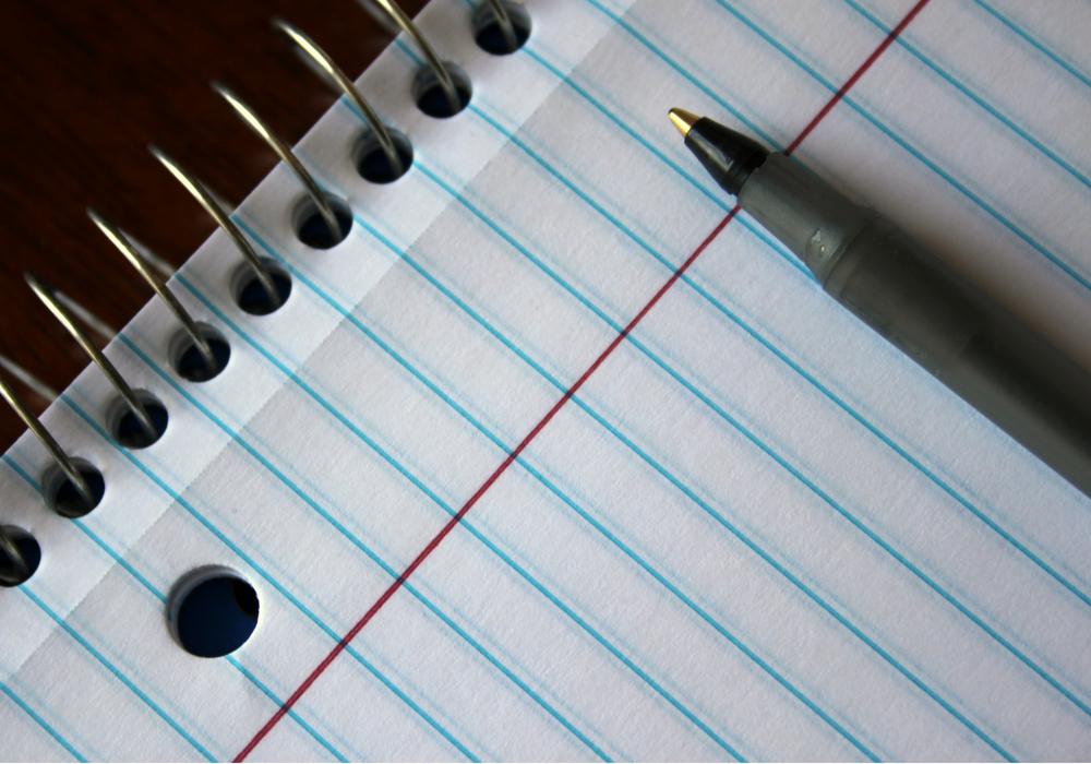 An artistic photo of a college-ruled notebook and a pen.