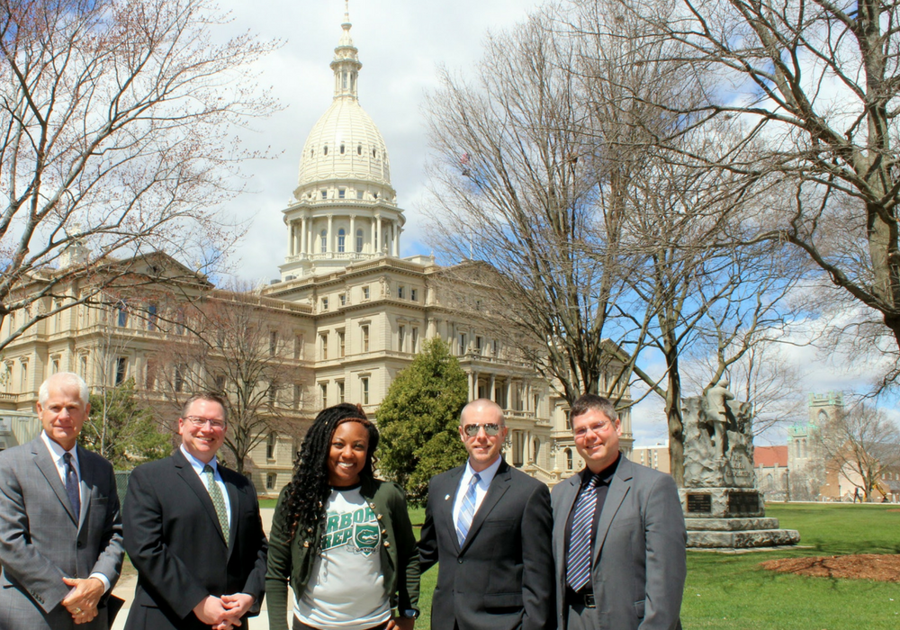 A photo of several charter school administrators in front of the Lansing, Michigan capitol building.