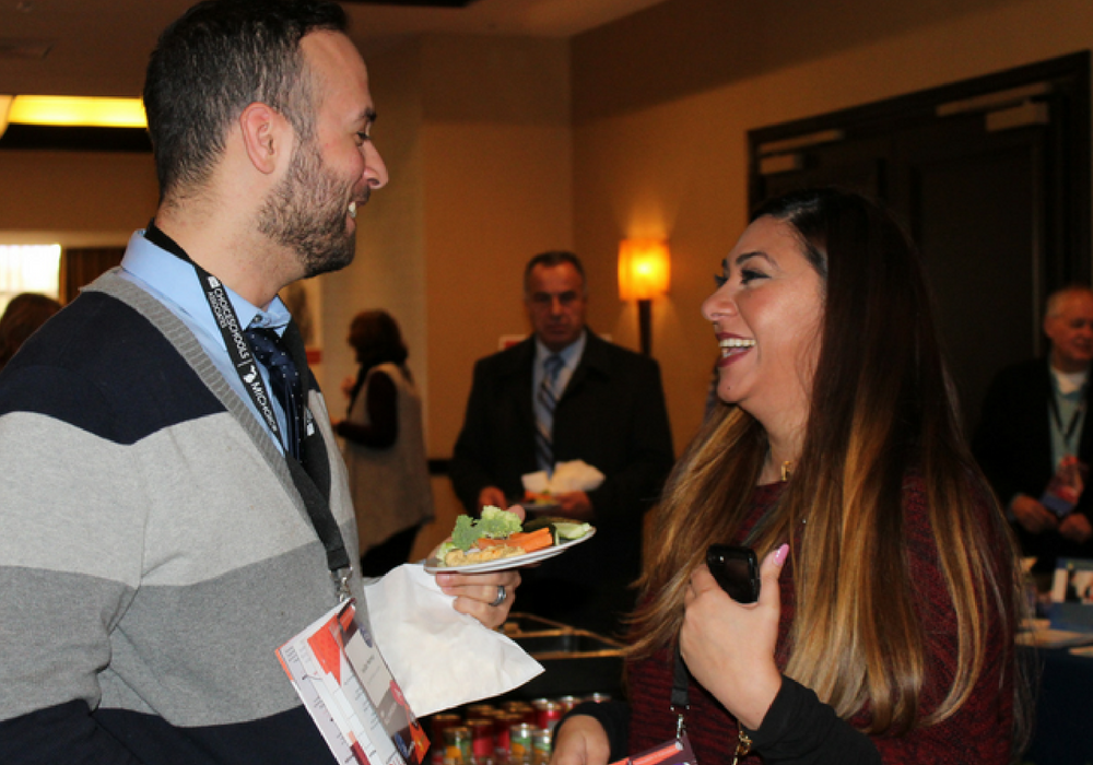 A photo of two professionals enjoying appetizers during the professional networking hour at the 2017 MI Charter School Symposium.