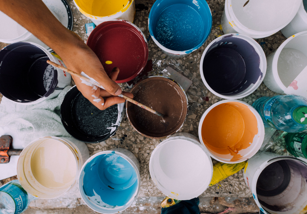 An artistic photo of several cups of paint, and a person's hand dipping a paintbrush into one cup.