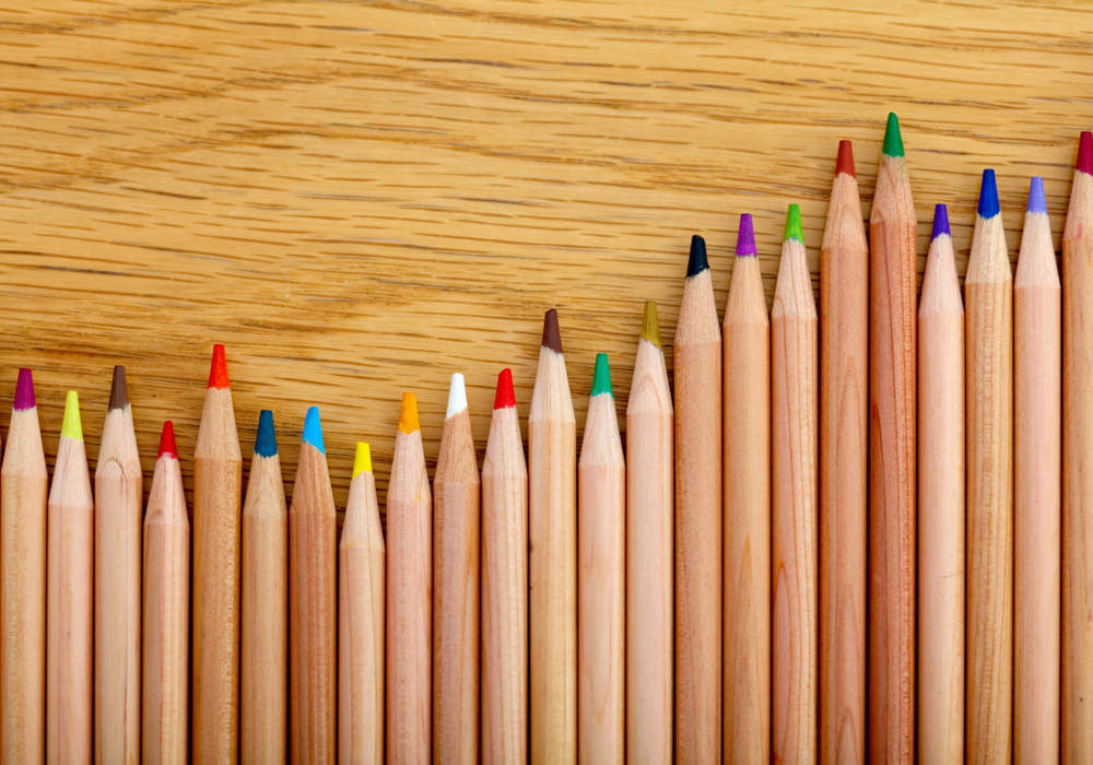 A photo of colored pencils arranged side by side at varying heights.
