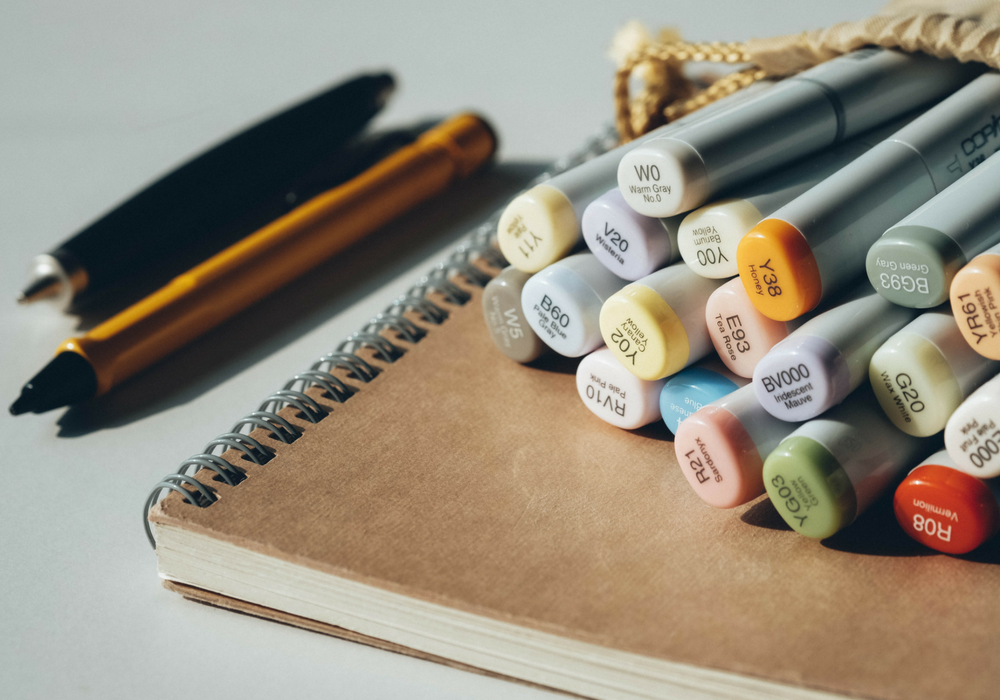 An artistic photo of a notebook and colorful pens.