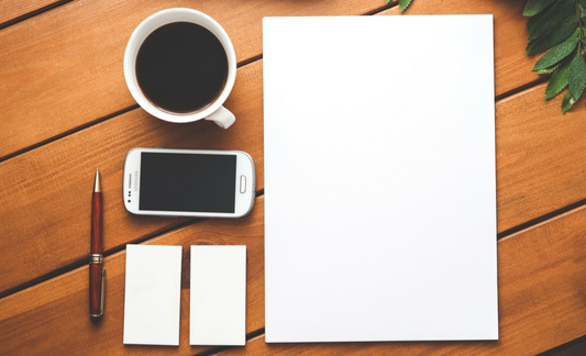 A photo of a piece of paper, cell phone, business cards, a pen and a cup of coffee.