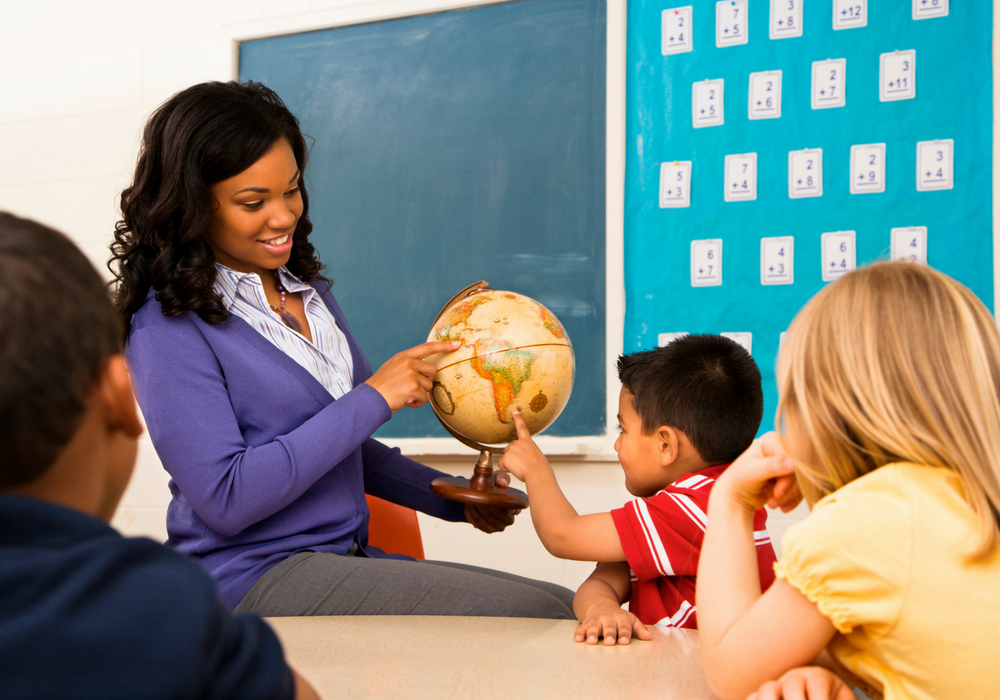 A photo of a female teacher showing a globe to several young students.