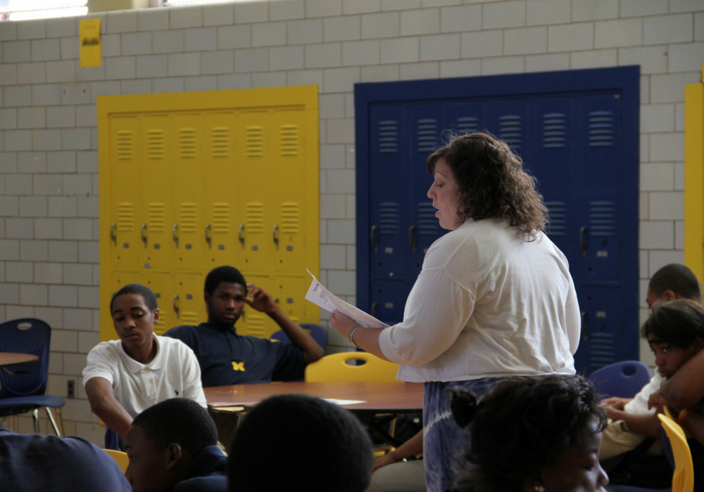 A photo of a female teacher instructing a classroom of students.