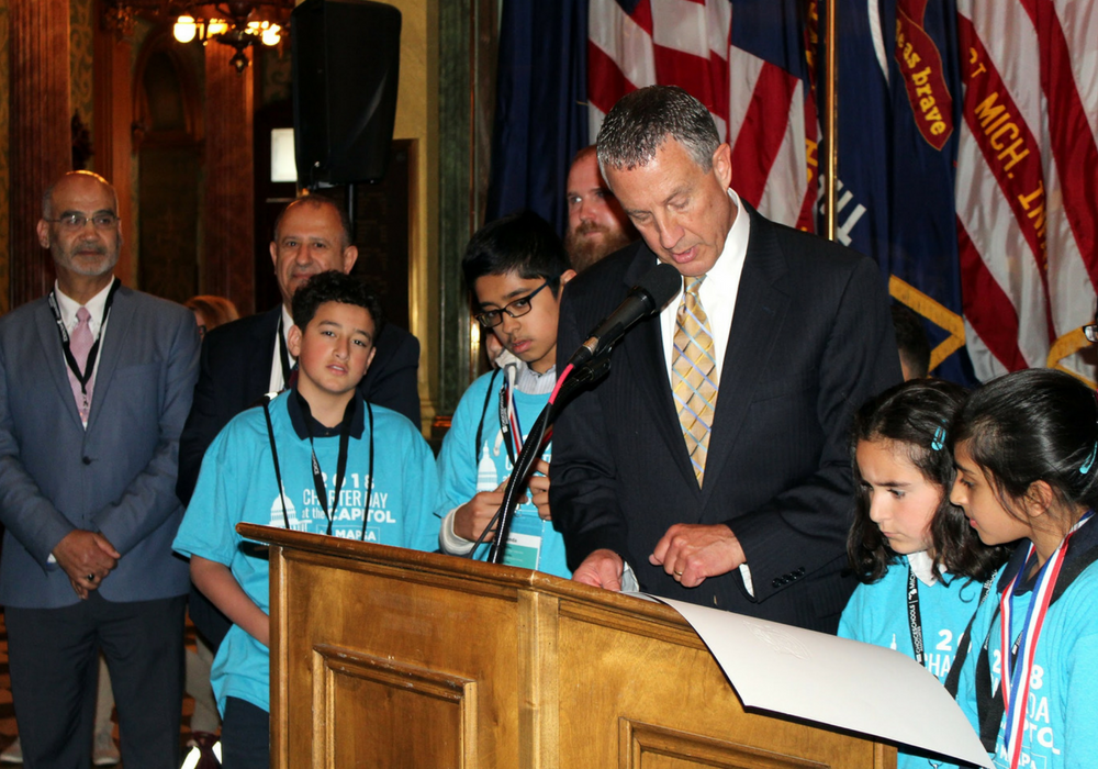 A photo of MAPSA President, Dan Quisenberry, presenting an award to several students at the 2018 Charter Day at the Capitol event.