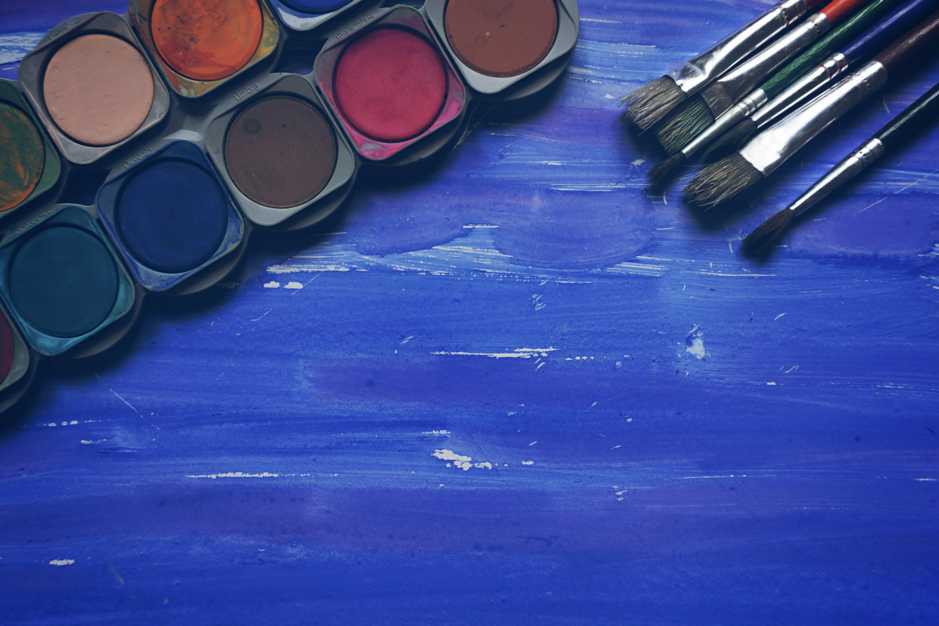 A photo of a paint set and paintbrushes atop a blue table.