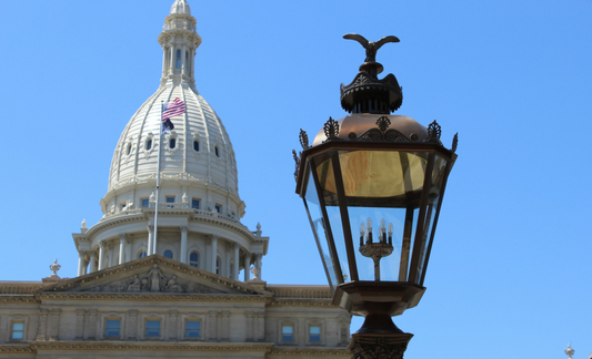 A photo of the Lansing Capitol building and a lantern.