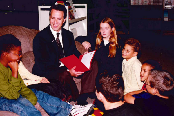 A historic photo of MAPSA President, Dan Quisenberry, reading to a group of students.
