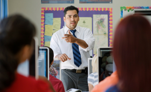 A photo of a man instructing students in a classroom.