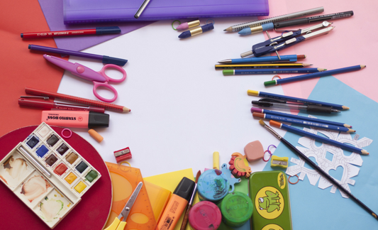 A colorful photo of school supplies and art supplies on a white table.