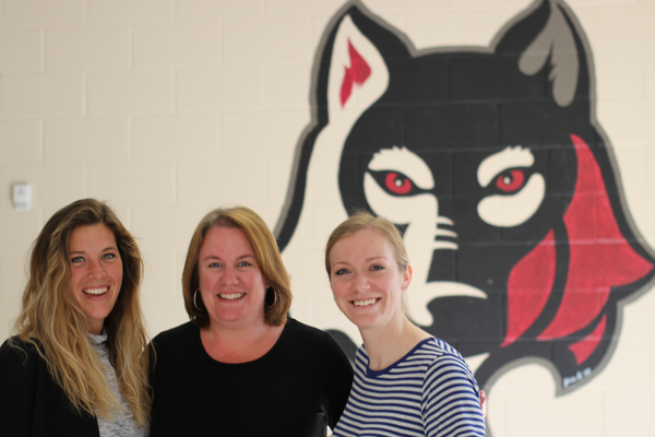 A photo of several educators posing in front of a mural of a large mascot.
