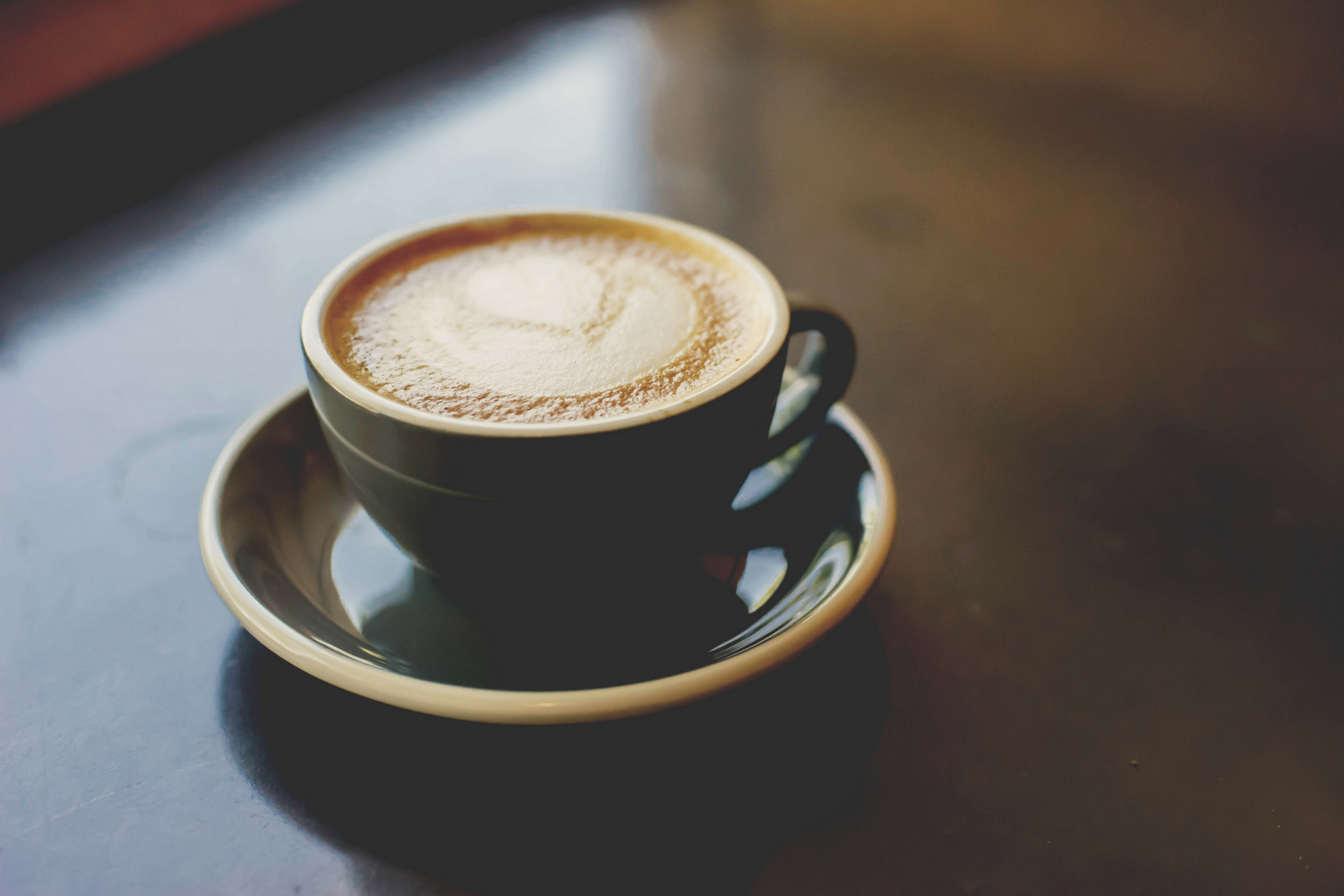 An artistic photo of a cup of coffee on a table.