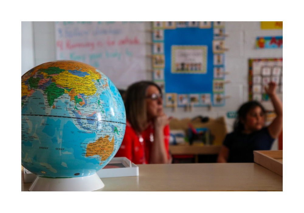 A student and teacher sit out of focus behind a globe.