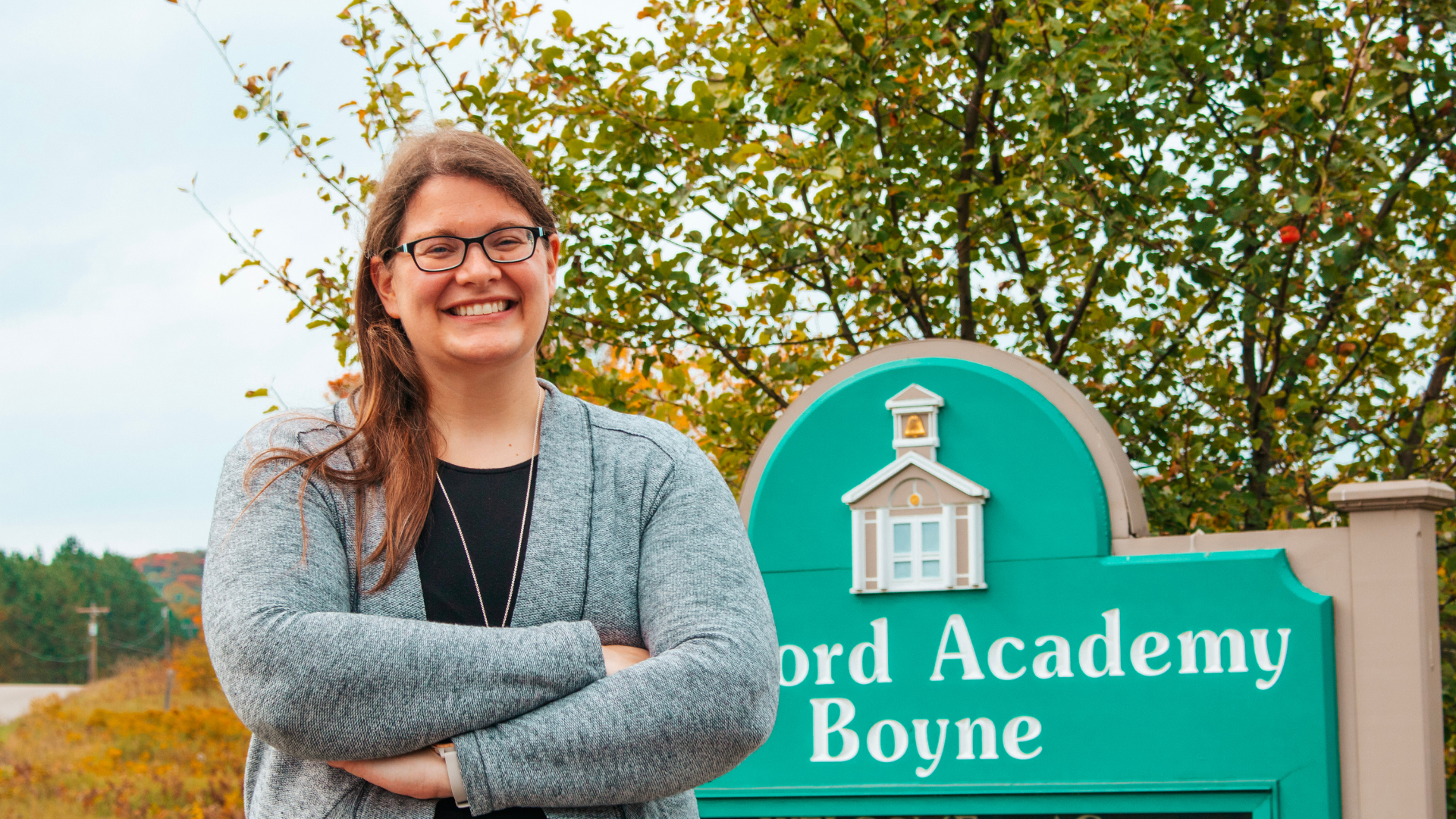 A photo of Concord Academy Boyne teacher, Caitlin Ritter, posing in front of her school sign amongst a backdrop of trees in full fall color.