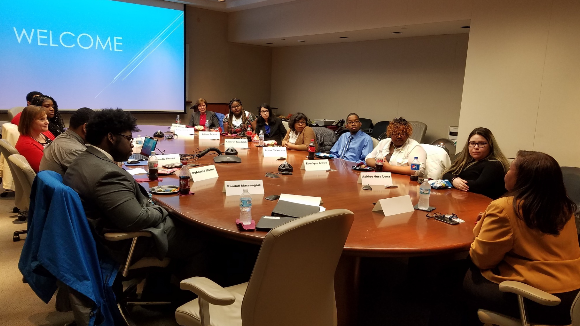 A group of students sits at a large boardroom table with Lisa Cash, the Vice President of Quality and New Product Launch at Ford Motor Company