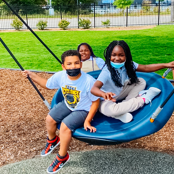 Students from Flint Cultural Academy swing of a tire swing