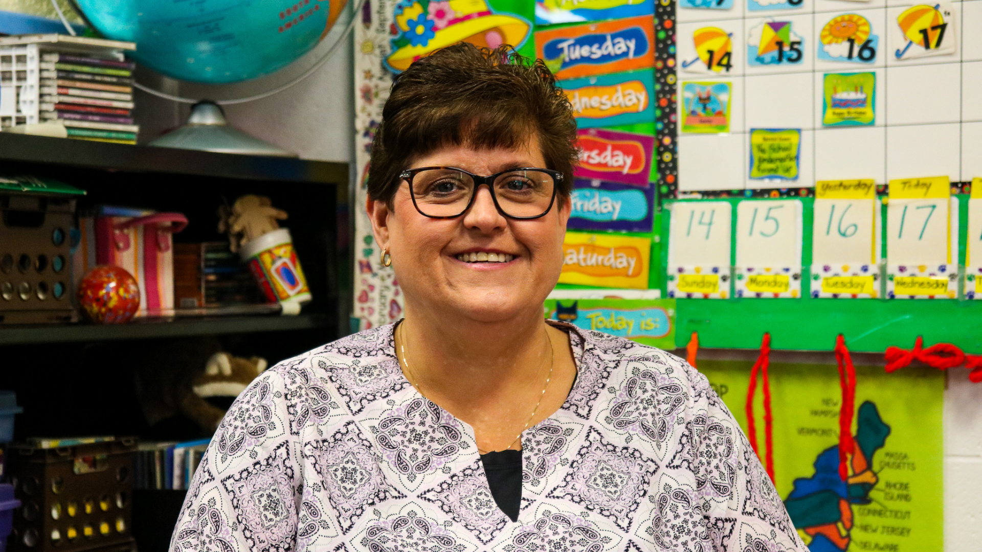 Teacher of the year, Jen Melero, stands smiling in her classroom