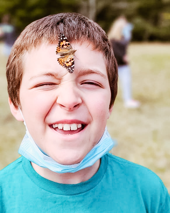 A white male student smiles while a butterfly rests on his forehead.