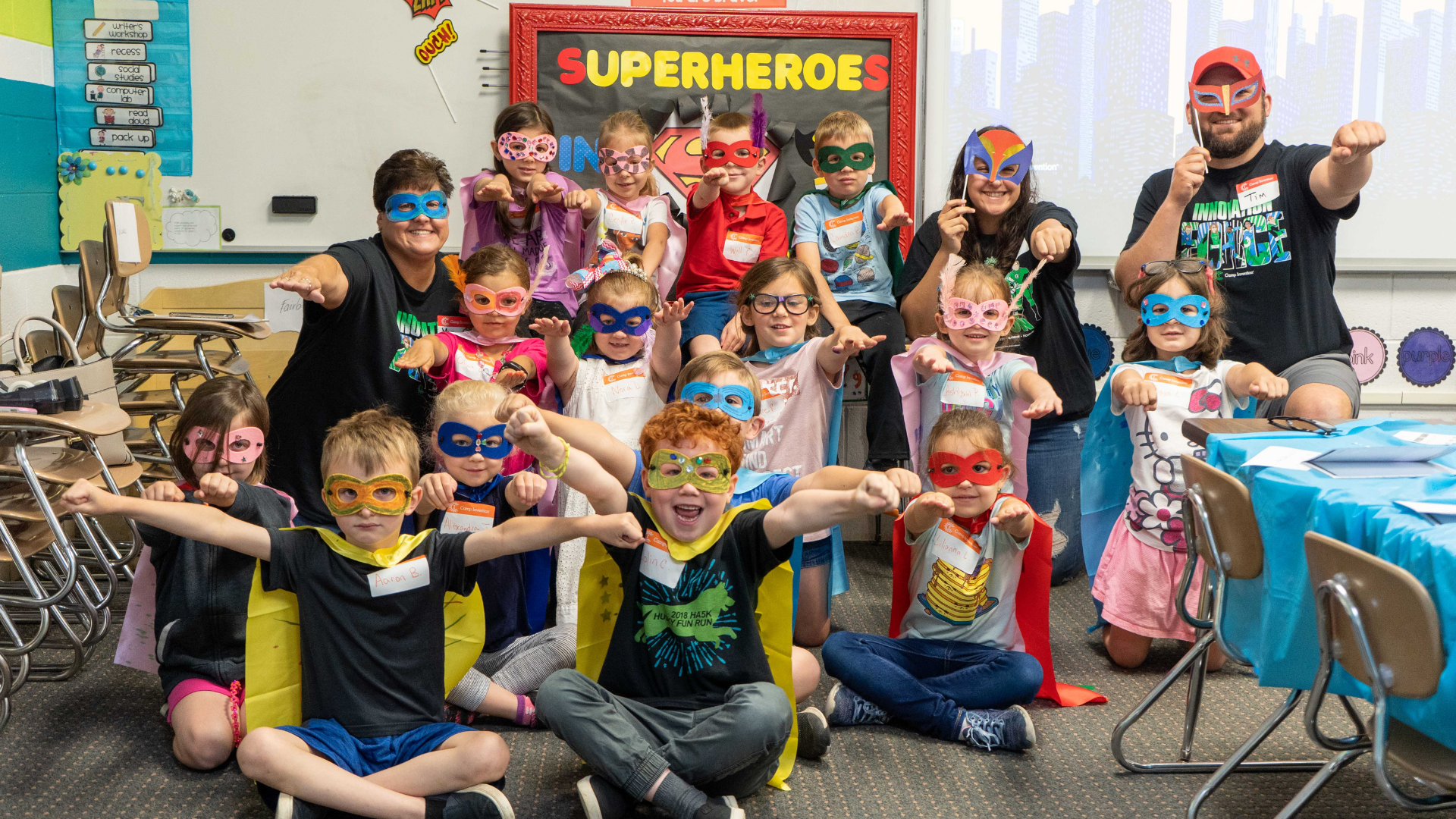 A group of students pose while dressed as superheroes in masks and capes.