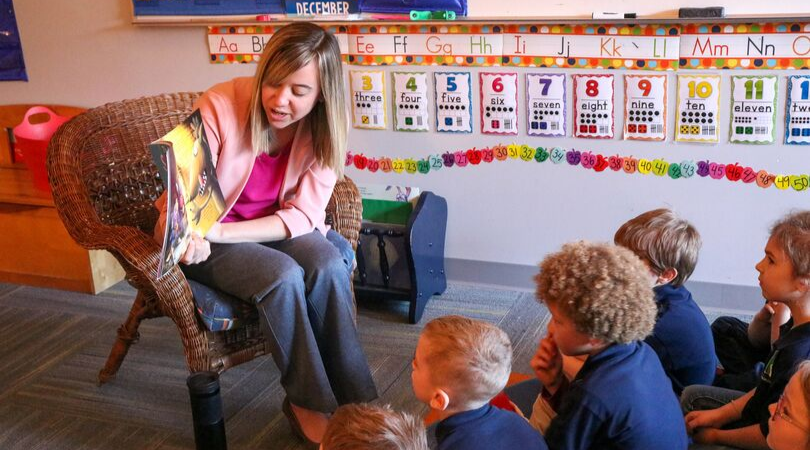 A photo of West MI Academy of Environmental Science elementary Principal, Kerri Barrett, sitting in a chair reading a book to a group of elementary students who are seated on the floor in front of her.