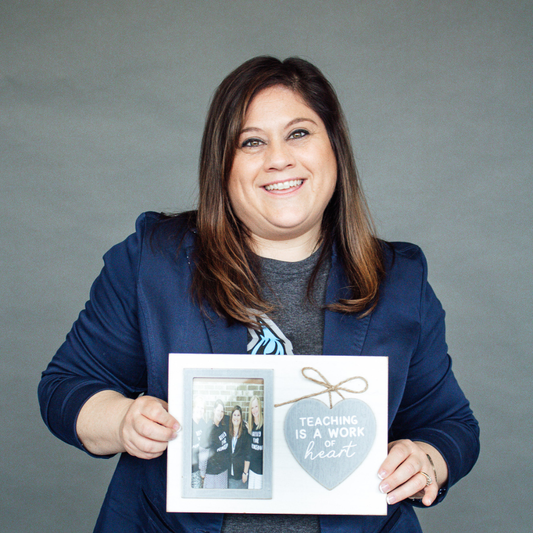 A headshot of Kelly Osterhout holding a photo frame reading
