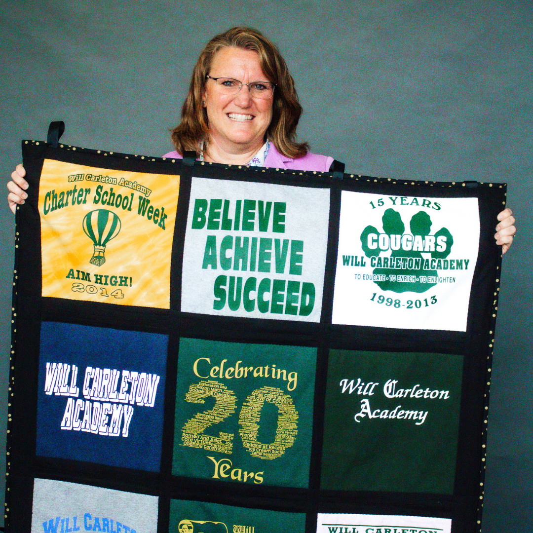 A headshot of 2021 AOY finalist, Colleen Vogt holding a quilt.