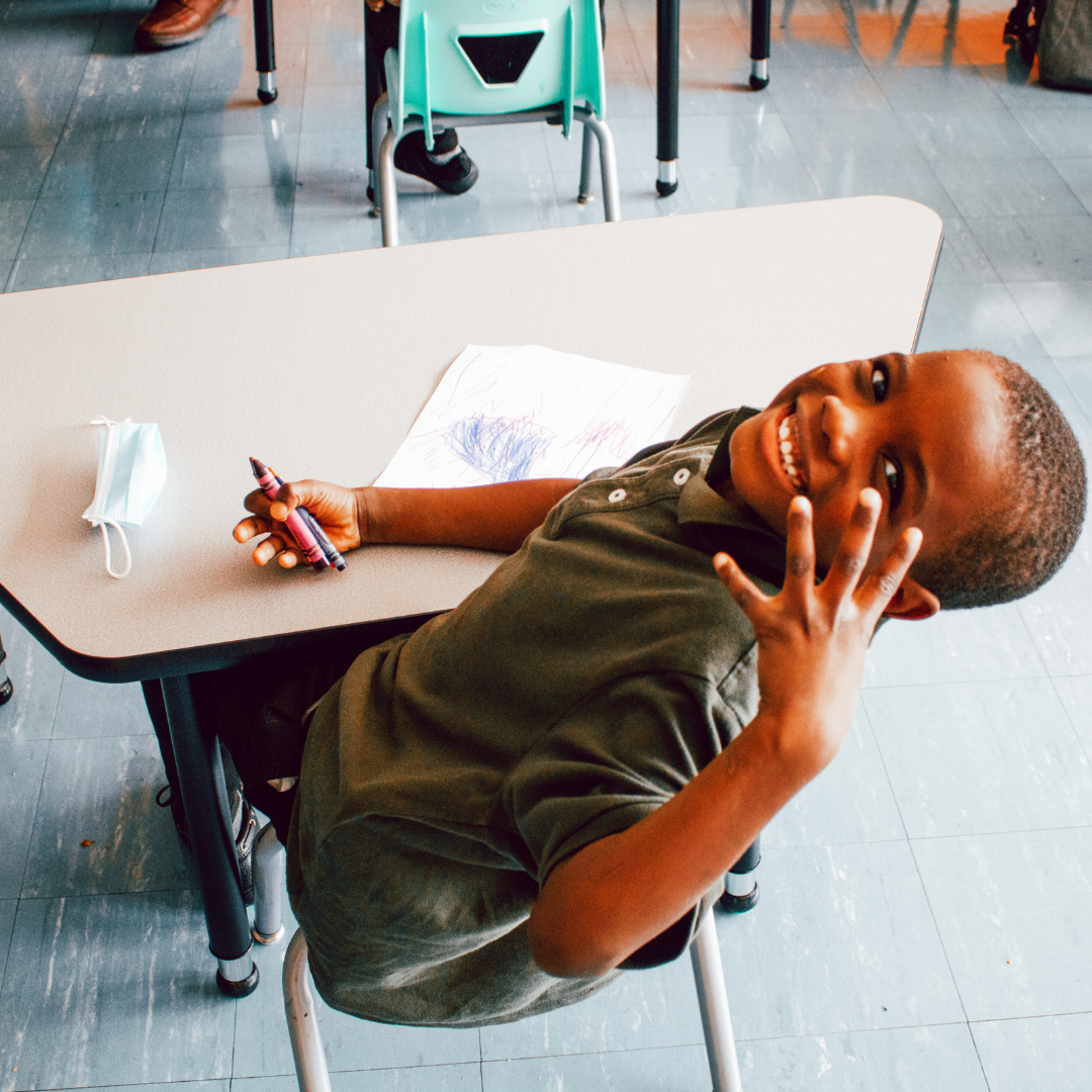 A photo of an elementary African American male student, posing for the camera at his seat in his classroom.
