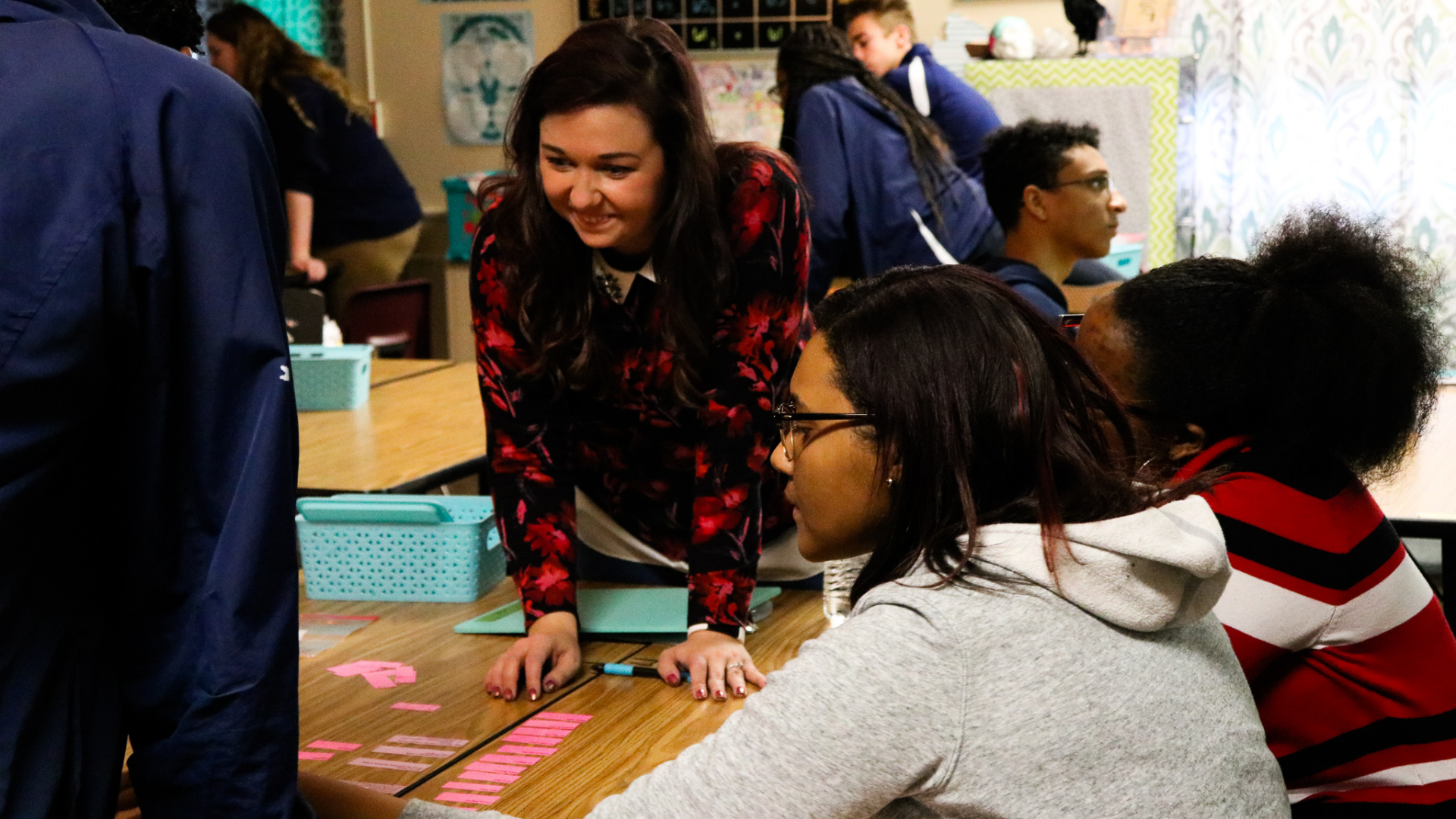 A photo of a high school classroom at Grand River Prep in Grand Rapids, where a female teacher is helping three students complete a group activity.