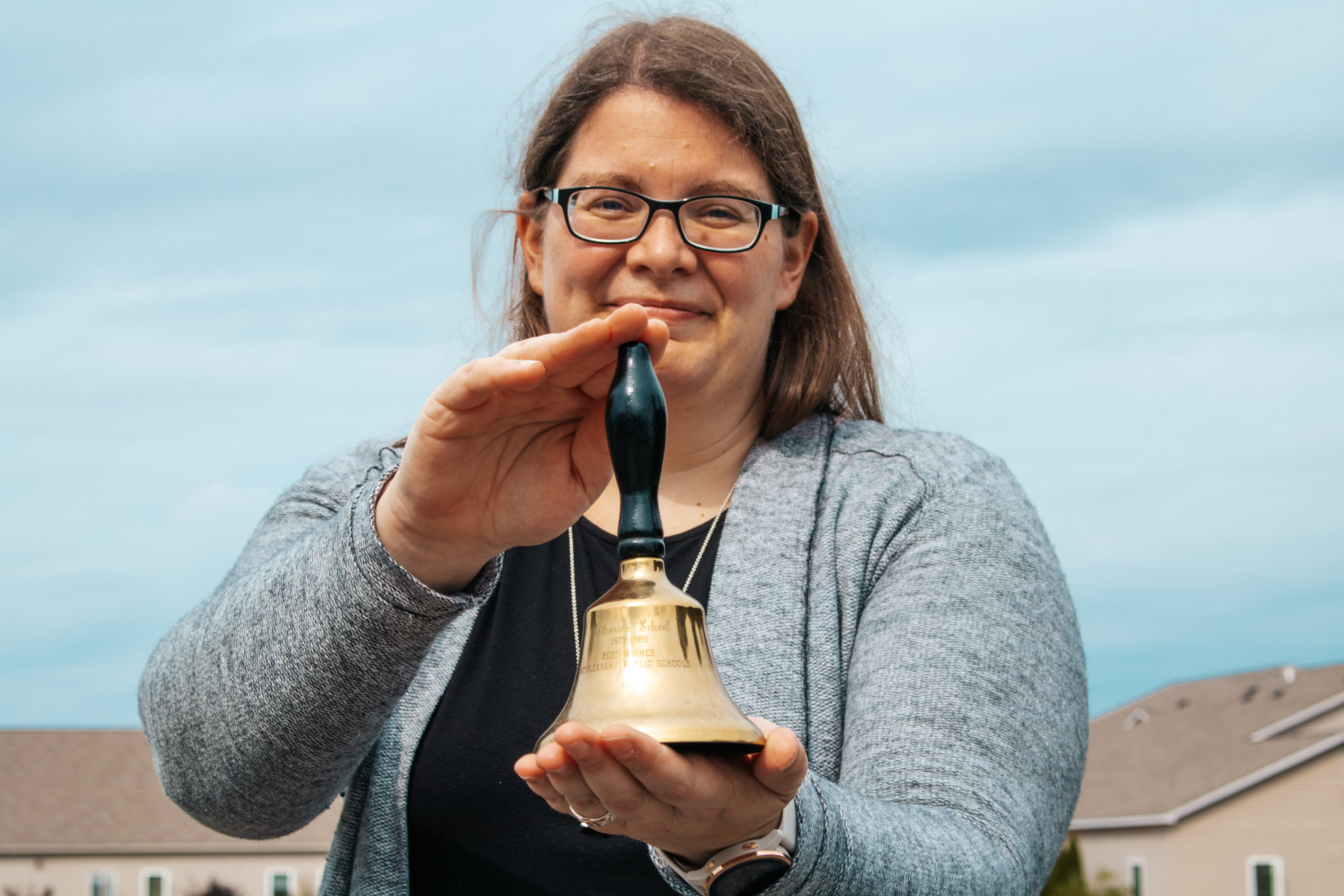 A photo of Concord Academy Boyne teacher, Caitlin Ritter, holding a bell that was given to her grandmother as a gift for her years of service as a teacher.