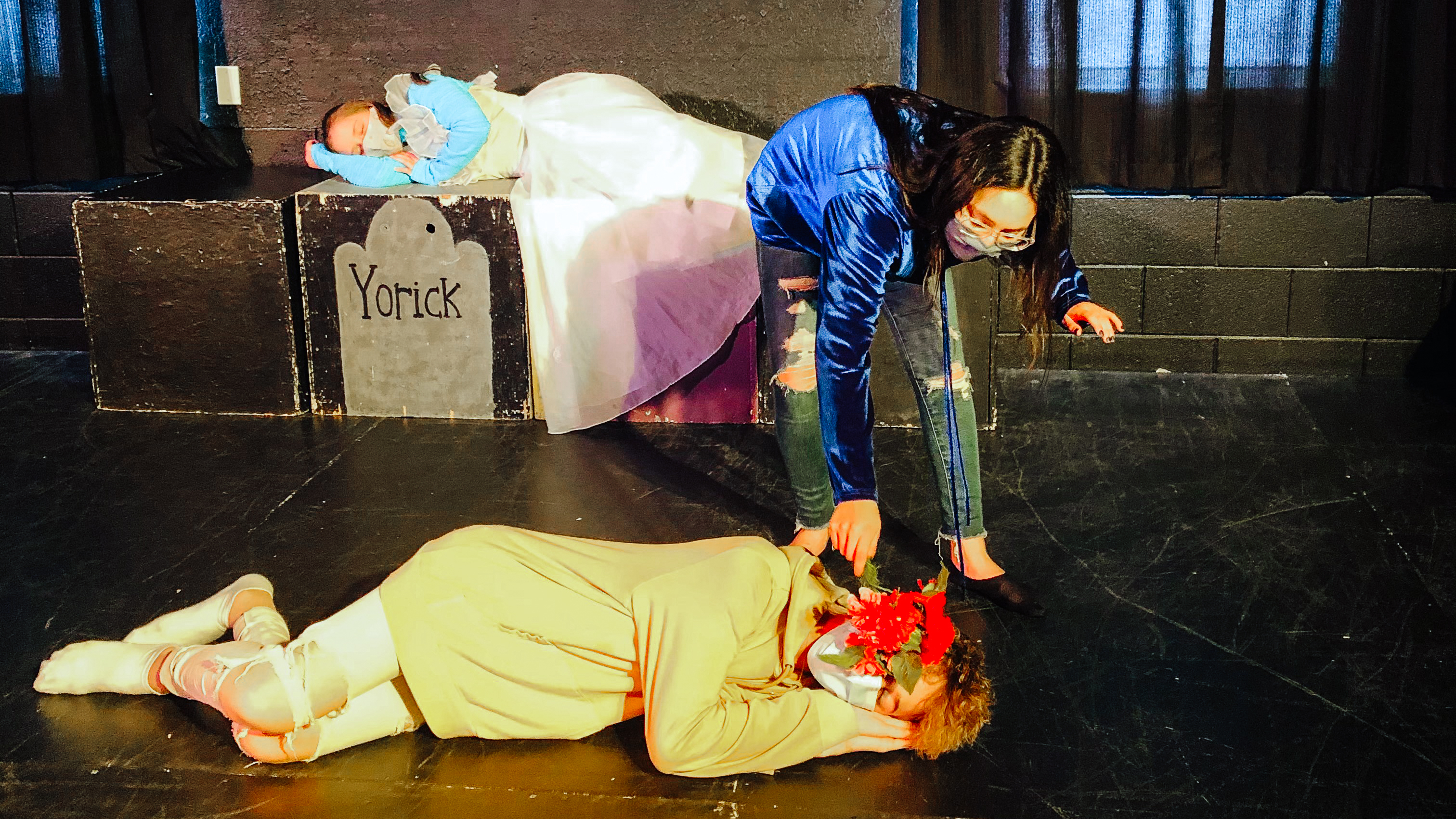 8th graders Lucy Herlein lays across a stage reaching down to another student during a production at West Michigan Academy of Arts and Academies