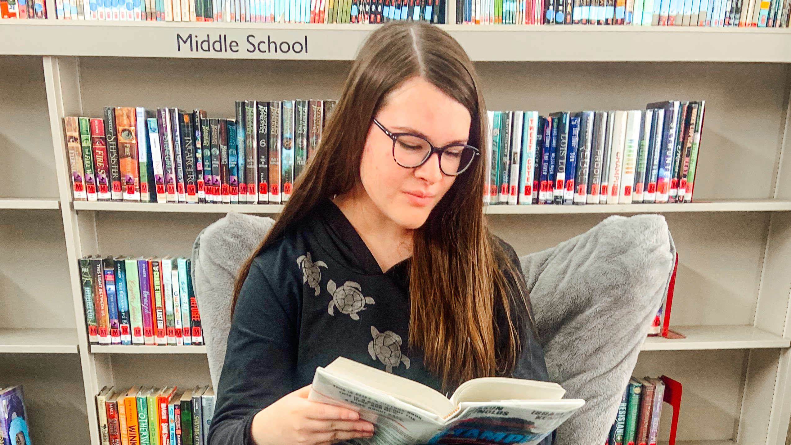 A photo of Kingsbury Country Day School 8th grader Ruby Howe sitting in a chair in the library reading a book.