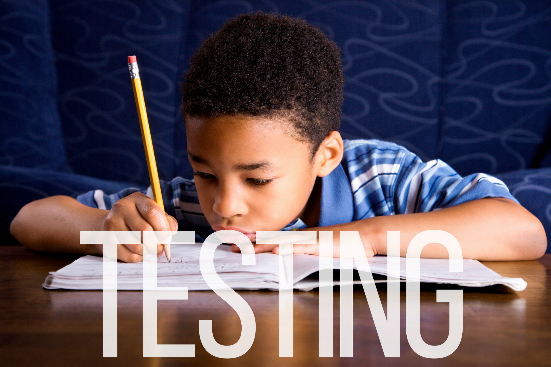 A photo of a young African American boy taking a test.