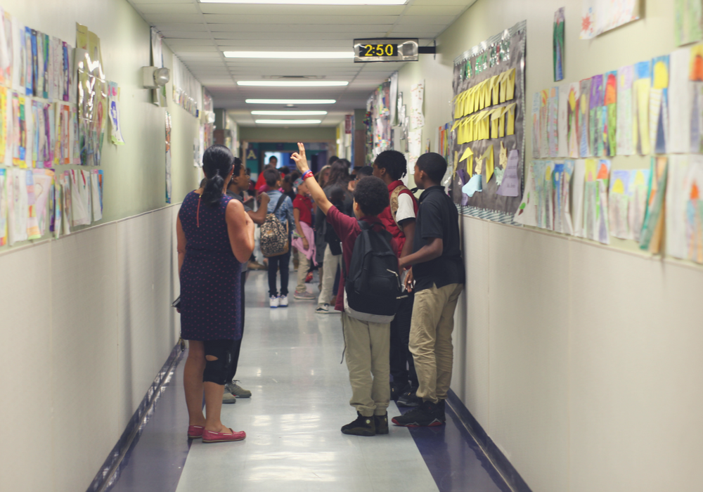 A photo of several students standing in a hallway and facing away from the camera.