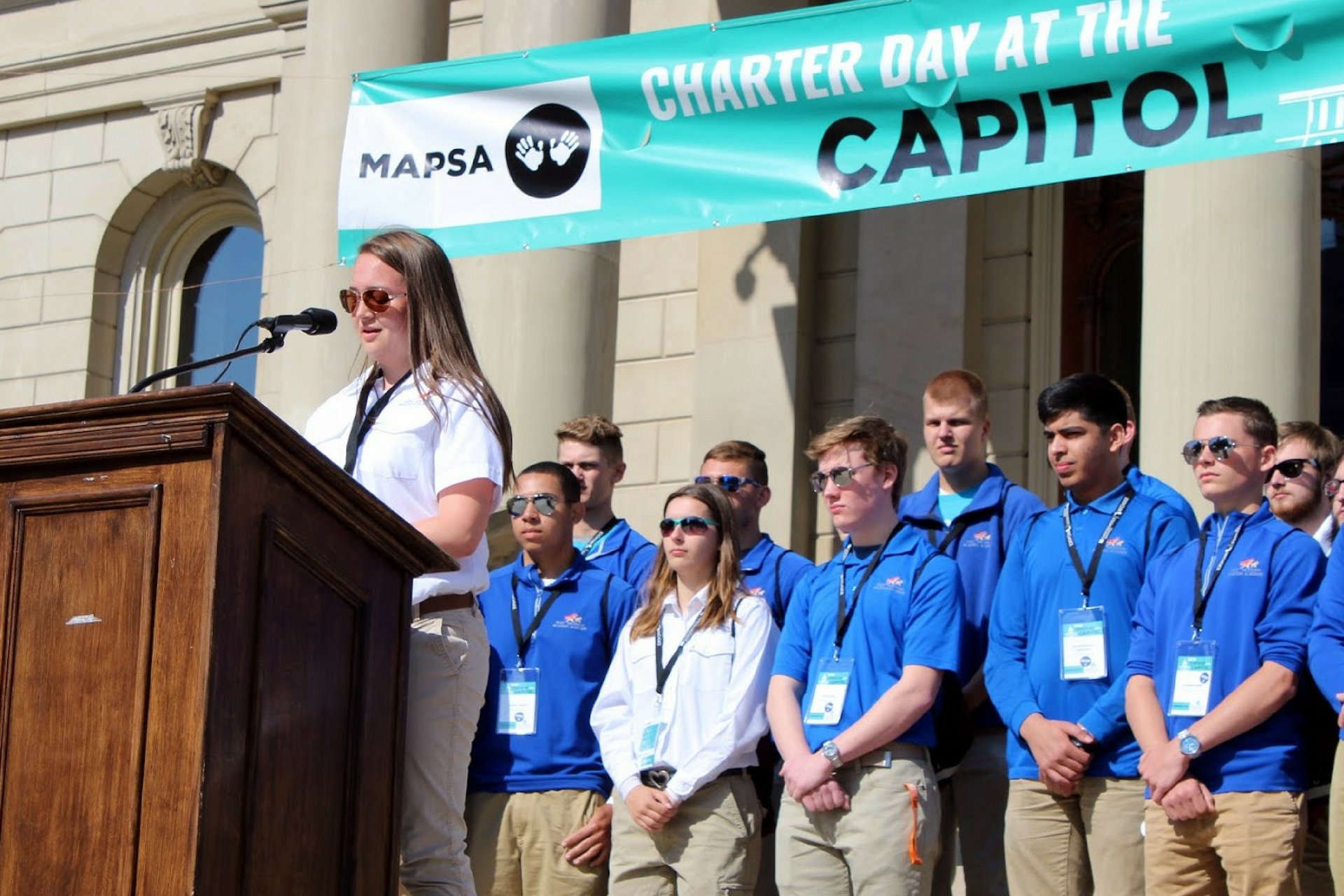 A photo of several students from West Michigan Aviation Academy on the Lansing Capitol steps during 2018 Charter Day at the Capitol.