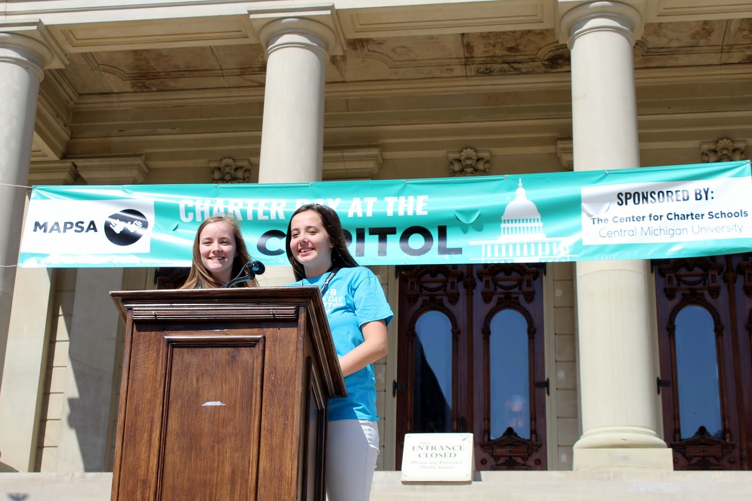 A photo of two girls giving a speech on the Lansing Capitol steps at the 2018 Charter Day at the Capitol celebration.